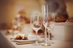Vidros ajustados com bebidas e pratos Foto de Stock