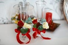 Vidros bonitos do casamento com laço, as flores brancas e as folhas do verde com fitas vermelhas Fotos de Stock