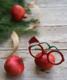 Vidros brancos verdes vermelhos dos espetáculos das romã do Natal com ramos de árvore decorativos do quadro e do abeto do feriado fotos de stock
