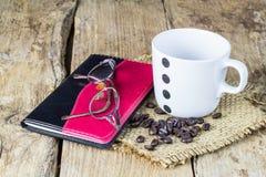 Vidros, caderno, canecas de café e feijões de café na tabela de madeira Foto de Stock