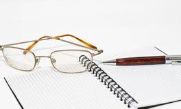 Vidros, caderno e a pena Foto de Stock