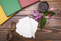 Vidros, caderno, flores e frasco dos cosméticos no fundo de madeira imagens de stock royalty free