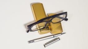 Vidros, caixa do ouro e pena pretos Fotografia de Stock Royalty Free