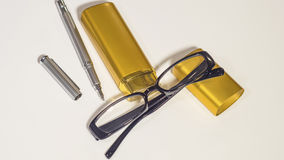 Vidros, caixa do ouro e pena pretos no fundo branco Foto de Stock Royalty Free