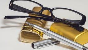 Vidros, caixa do ouro e uma pena Fundo branco do isolado closeup Foto de Stock Royalty Free