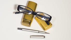 Vidros, caixa do ouro e uma pena fundo do branco do isolado Foto de Stock Royalty Free