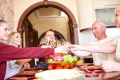 Vidros cheering da família feliz no Natal em um fundo borrado Comensal da ação de graças Comemorando o conceito Imagem de Stock