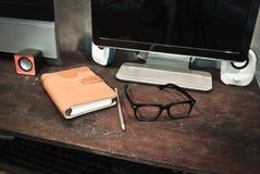 Vidros com caderno em uma mesa. Fotografia de Stock