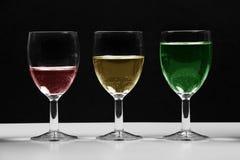 Vidros com carta de negócio crescente colorida da água imagem de stock