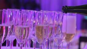 Vidros com champanhe na tabela de bufete no salão do restaurante, em uma tabela shurshetny com vidros e no champanhe no vídeos de arquivo