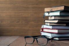 Vidros com os livros do livro encadernado na tabela de madeira Espaço livre para o texto Imagem de Stock