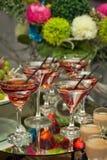 Vidros com palhas no fundo das flores Foto de Stock Royalty Free