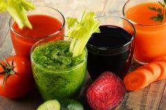 Vidros com sucos vegetais orgânicos frescos na tabela de madeira Imagens de Stock