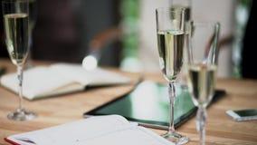 Vidros com suporte do champanhe na tabela em uma reuni?o de neg?cios filme