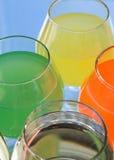 Vidros com verde, amarelo, água em um espelho Fotografia de Stock