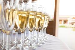 Vidros com vinho espumante em um partido exterior em um dia ensolarado foto de stock