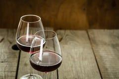 Vidros com vinho tinto no fundo de madeira rústico Imagens de Stock