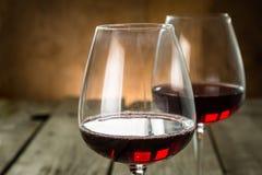 Vidros com vinho tinto no fundo de madeira rústico Imagem de Stock Royalty Free
