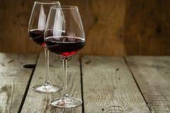 Vidros com vinho tinto no fundo de madeira rústico Imagens de Stock Royalty Free