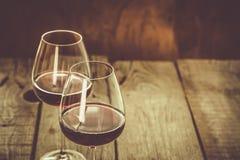 Vidros com vinho tinto no fundo de madeira rústico Fotografia de Stock Royalty Free