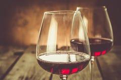Vidros com vinho tinto no fundo de madeira rústico Foto de Stock Royalty Free