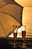 Vidros com vinho tinto no por do sol com guarda-chuva Fotos de Stock Royalty Free