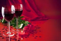 Vidros com vinho, uma vela e as rosas Fotos de Stock