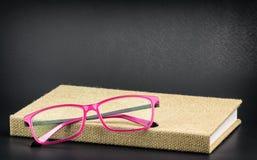 Vidros cor-de-rosa brilhantes em um livro Imagens de Stock Royalty Free