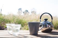 Vidros da água, do potenciômetro do chá e da caneca na tabela de madeira, no acampamento e no T Fotos de Stock Royalty Free
