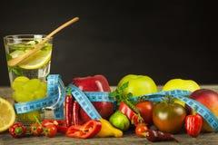 Vidros da água e de um medidor do ` s do alfaiate Frutas e verdura O conceito da perda de peso Dieta saudável Imagem de Stock Royalty Free