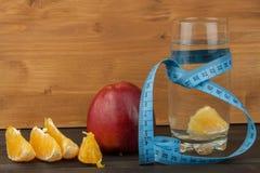 Vidros da água e do fruto Alimento para o perca de peso Apple sobre o caderno Dieta controlada Dieta saudável para atletas Foto de Stock Royalty Free