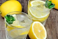 Vidros da água fresca com limão e hortelã na tabela de madeira Fotografia de Stock Royalty Free