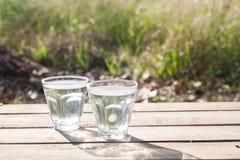 Vidros da água pura na tabela de madeira com natureza no fundo, Fotografia de Stock Royalty Free