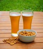 Vidros da cerveja e da bacia de pretzeis Fotografia de Stock
