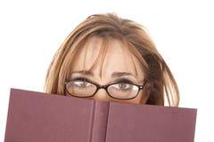 Vidros da mulher que olham sobre o livro Imagens de Stock Royalty Free
