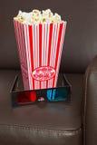 Vidros da pipoca 3D e cadeira do cinema. Foto de Stock