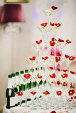 Vidros da pirâmide do champanhe com azeitonas e as pétalas cor-de-rosa Fotos de Stock Royalty Free