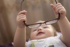 Vidros da posse do bebê em suas mãos pequenas imagem de stock royalty free