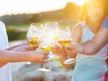 Vidros da terra arrendada dos povos da factura de vinho branco um brinde Imagem de Stock