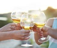 Vidros da terra arrendada dos povos da factura de vinho vermelho um brinde Foto de Stock