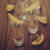 Vidros da vodca com o limão no fundo de madeira tonificando a imagem Imagens de Stock