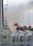 Vidros de água do café e janela chuvosa da garrafa Fotografia de Stock