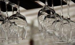 Vidros de aguardente claros que penduram no cupholder de madeira Imagens de Stock