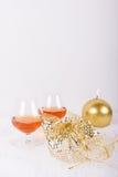 Vidros de aguardente com vela e a decoração douradas Fotos de Stock
