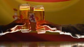 Vidros de cerveja do tinido dos homens, bandeira espanhola no fundo, aficionados desportivos que descansam no bar vídeos de arquivo