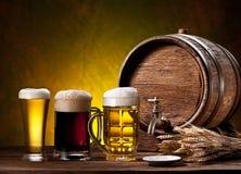 Vidros de cerveja, tambor velho do carvalho e orelhas do trigo. Fotos de Stock Royalty Free
