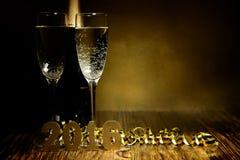 Vidros de figuras 2016 do champanhe e do ouro em um backg de madeira Foto de Stock Royalty Free