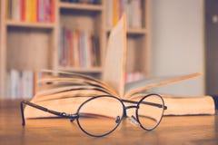Vidros de leitura na tabela com fundo do livro e da caixa de livro Fotografia de Stock Royalty Free