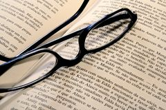 Vidros de leitura no livro Imagens de Stock Royalty Free