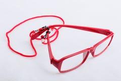 Vidros de leitura vermelhos com uma correia vermelha do pescoço em uma superfície branca Fotos de Stock